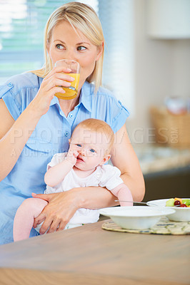 Buy stock photo A mother and her adorable baby girl sitting in the kitchen enjoying breakfast