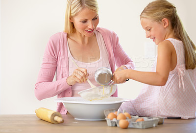 Buy stock photo A little girl sitting on a kitchen counter and helping her mother bake