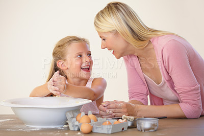 Buy stock photo A mother and daughter having fun while baking