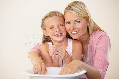 Buy stock photo Portrait of a smiling mother and daughter kneading cookie dough together