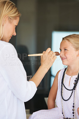 Buy stock photo Little girl having make-up applied by her mother with a smile