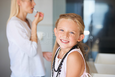 Buy stock photo Little girl sitting with her mother as she applies her makeup