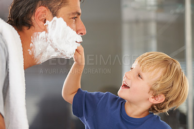 Buy stock photo A young boy shaving his father's beard