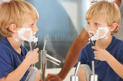 Buy stock photo A young boy with a face full of shaving cream looking in the mirror