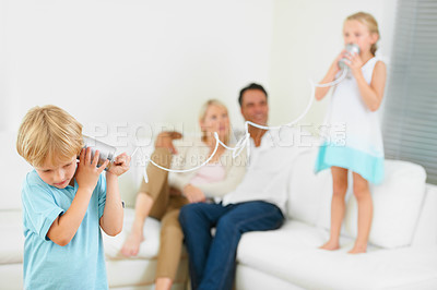 Buy stock photo A little boy shouting loudly into a tin can connected to another that his sister is holding