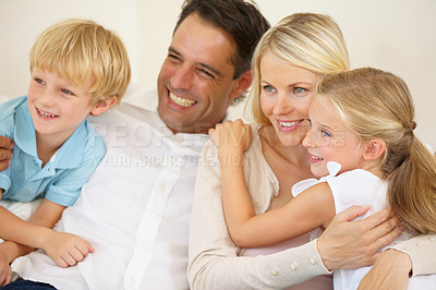 Buy stock photo A loving family of four watching television together in the lounge