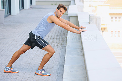 Buy stock photo Young jogger doing some stretches outside