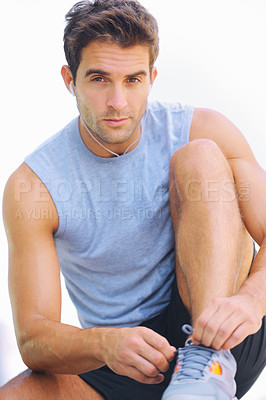 Buy stock photo Handsome young man looking at the camera while tying his shoelaces