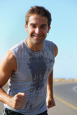 Buy stock photo Handsome young athlete smiling at the camera while jogging