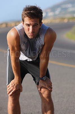 Buy stock photo Tired young runner leaning over to catch his breath