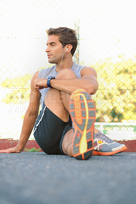 Buy stock photo Young handsome athlete stretching his legs while listening to music
