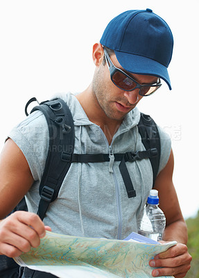 Buy stock photo Closeup of handsome young hiker reading a map