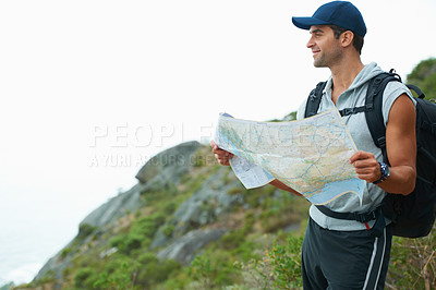 Buy stock photo Young hiker holding a map while appreciating the view