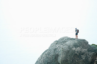 Buy stock photo Full length of a hiker standing on a mountain top looking at the view