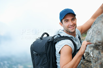 Buy stock photo Young climber smiling at the camera as he scales the top of a cliff