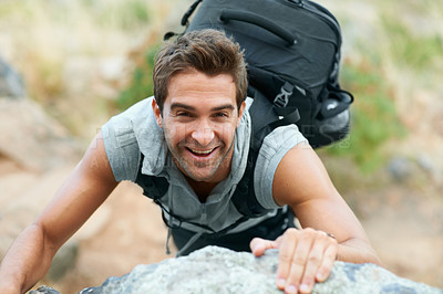 Buy stock photo Young mountain climber smiling up at the camera