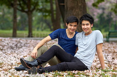 Buy stock photo Cute young gay Asian couple smiling together while sitting in the park