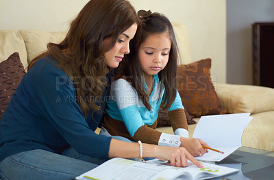 Buy stock photo Little girl getting help with her homework from her mother