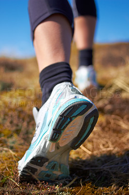 Buy stock photo A cropped shot of a woman's running shoe as she is running on a nature trail
