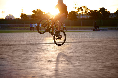 Buy stock photo Shot of a man doing tricks on his bike, with sun flare