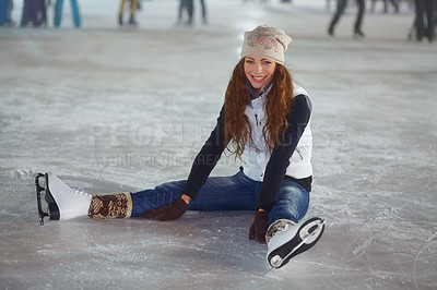 Buy stock photo A young woman smiling while sitting down on the ice of a skating rink