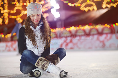 Buy stock photo Shot of a woman sitting on sitting on an ice rink
