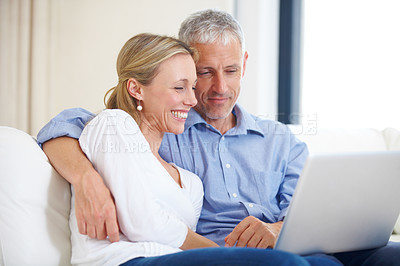 Buy stock photo A young married couple sitting together on the sofa with their laptop