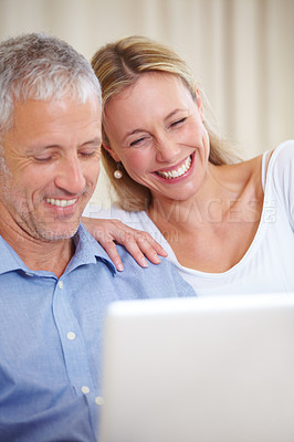Buy stock photo A married couple sitting with their laptop and smiling happily