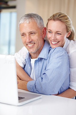 Buy stock photo A wife embracing her husband as he works on the laptop