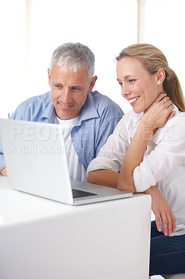 Buy stock photo A mature couple looking relaxed as they work on their laptop at home