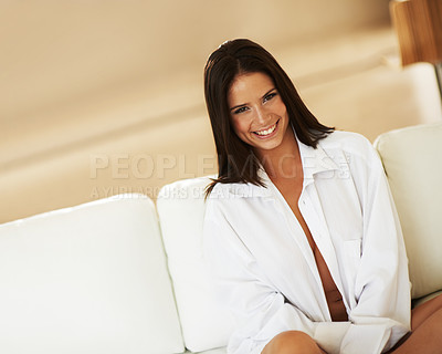 Buy stock photo Gorgeous young brunette sitting on a couch wearing only a white shirt