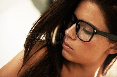 Buy stock photo Closeup of a lovely young brunette wearing glasses looking downwards - profile
