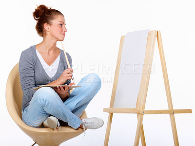 Buy stock photo Studio shot of a young female artist sitting on a chair looking at a blank canvas
