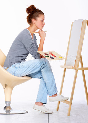Buy stock photo Studio shot of a young woman sitting on a chair looking at a blank canvas