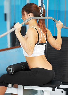 Buy stock photo Rear view of an attractive young woman working her shoulders in the gym