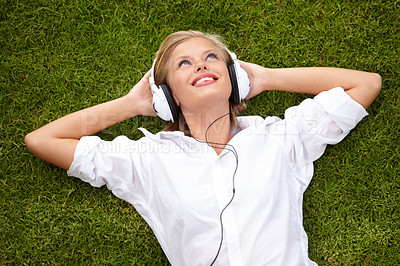 Buy stock photo High angle shot of a woman lying on a grassy field listening to musicHigh angle shot of a woman lying on a grassy field listening to music with her eyes closed