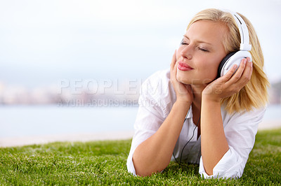 Buy stock photo Shot of a woman lying on a grassy field listening to music with her eyes closed