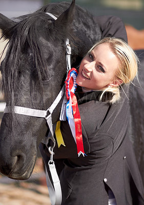 Buy stock photo Shot of a young rider hugging her mount affectionately after winning a competition