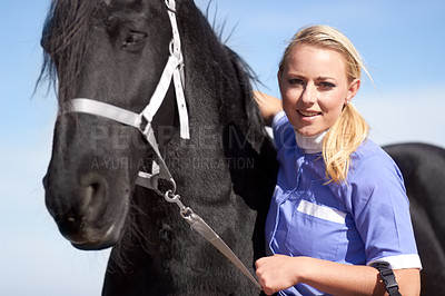 Buy stock photo Portrait of a horse trainer affectionately stroking her horse while holding it by the bridle