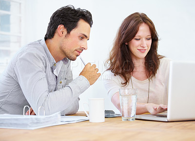 Buy stock photo Shot of a two young design professionals sitting together and discussing something on a laptop