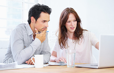 Buy stock photo Shot of a two young  professionals sitting together and discussing something on a laptop
