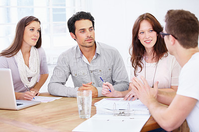 Buy stock photo Shot of a group of young design professionals sitting at a table and having a brainstorming session