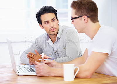 Buy stock photo Shot of two young business professionals having a discussion over a laptop