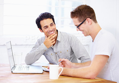 Buy stock photo Shot of two happy-looking business professionals having a conversation over a laptop