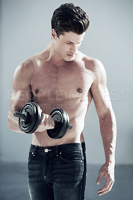 Buy stock photo A good looking man with no shirt on lifting weights