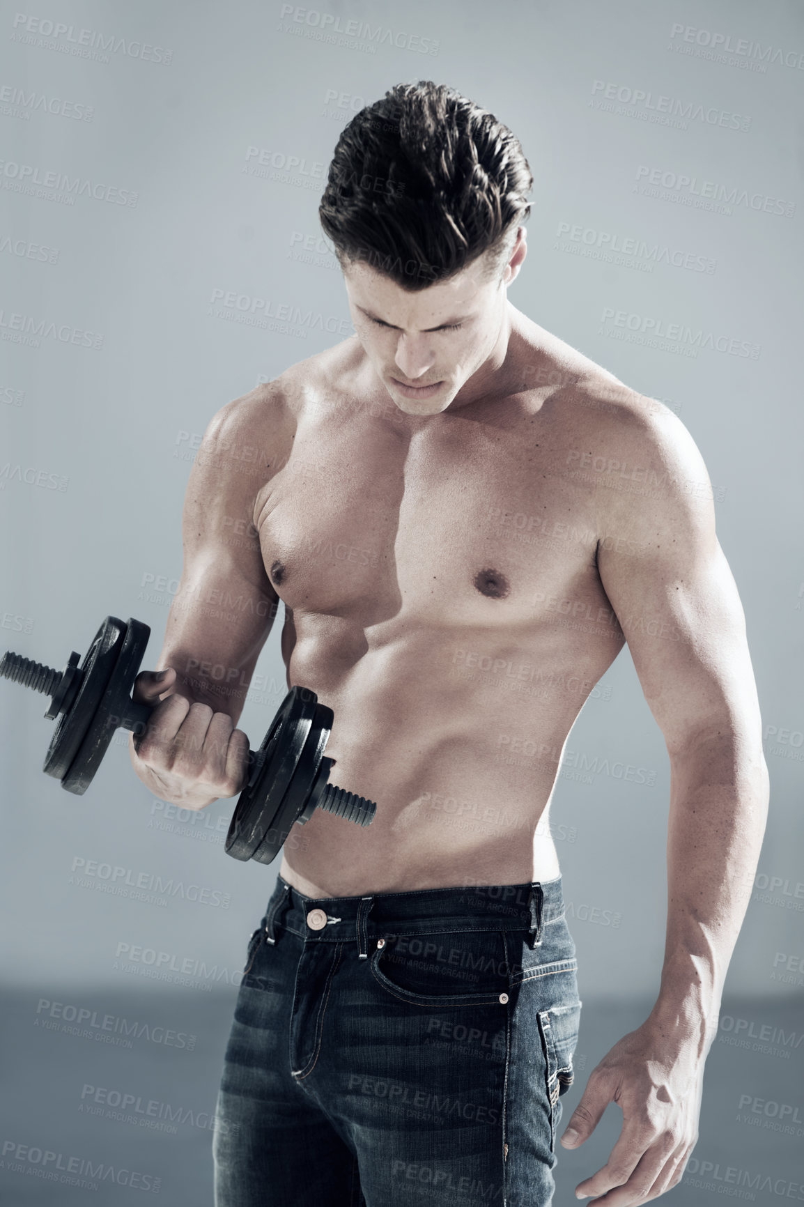 Buy stock photo A handsome male in jeans and no shirt lifting weights