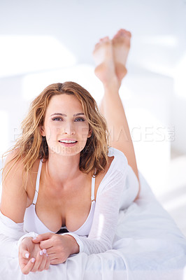 Buy stock photo Portrait of a smiling woman lying on her bed with her bra exposed