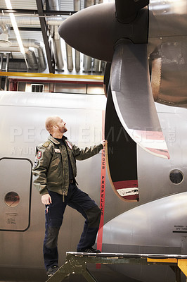 Buy stock photo Full length shot of a pilot inspecting the propellor of his plane