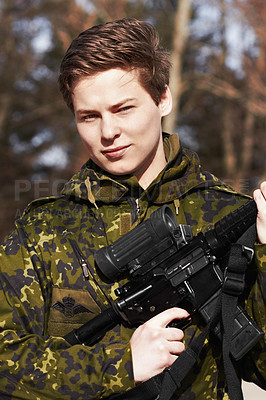 Buy stock photo A young soldier standing with a rifle