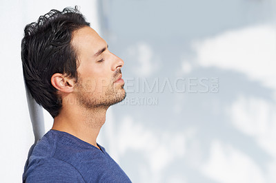 Buy stock photo A handsome young man standing outside and relishing the sunshine